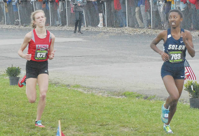 David Fong | Miami Valley Today file Troy's Morgan Gigandet (left) gets ready to pass Solon's Olivia Howell to win a state championship at the 2017 Division I state cross country meet at National Trail Raceway in Hebron. The OHSAA announced Wednesday that the state cross country meets would move to Fortress Obetz in Columbus.