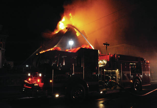 Firefighters from Bradford, Covington and Piqua battle a house fire in the 400 block of North Miami Street in Bradford on Monday night. A 12-year-old boy lost his life in the blaze.