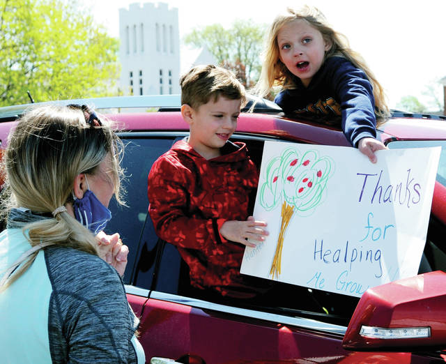 Hunter, 6, and Aliyiah, 7, Steinke of Piqua hold a sign thanking one of their pre-school teachers, Miss Anita Polakowski, at Piqua Catholic School on Wednesday. Principal Brad Zimmerman organized the Teacher Appreciation Day event to allow both students and teachers an opportunity to visit, at a safe distance, before the school year ends. The Teacher Appreciation Day event was timed in order to allow only one teacher and their class at a time to meet in the parking lot where parents and students honked their horns and waved signs.