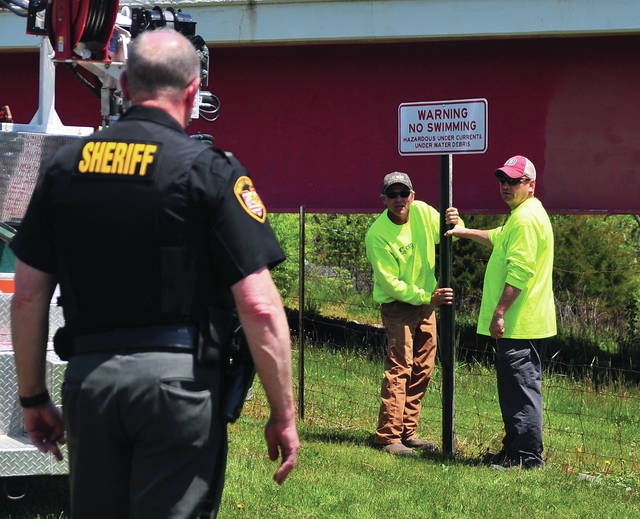 """Miami County Highway Department workers Bart Weer and Bruce Johnson look to Lt. Chris Bobb of the Miami County Sheriff's Office to ensure the newly-erected signs stating """"No Swimming"""" at Ludlow Falls is straight."""