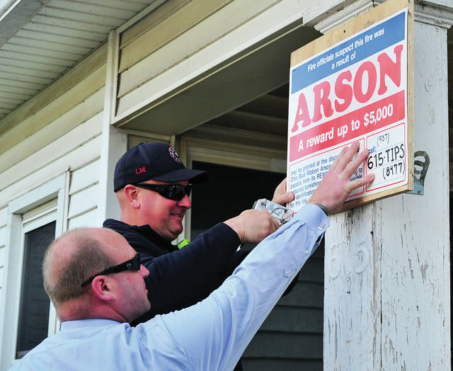 Detective Brett Marrs of the Piqua Police Department holds a sign as Piqua Firefighter Cleadous Hawk staples it to the porch on Wednesday.