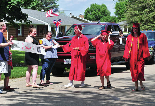 """Troy High School Class of 2020 graduates Nicholas Matthews, Ashlee Harmon, and Caitlyn Hutson, l-r, enjoy a parade through their Stonewood Drive neighborhood on Saturday. The trio graduated earlier in the day and family and neighbors organized the celebration to give them a """"proper send-off""""."""