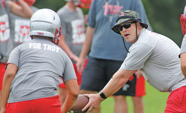 Lee Woolery   Miami Valley Today file Troy football coach Dan Gress runs drills during a practice last summer.