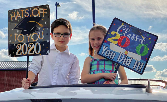 Graham Baker, 9, (left) and Sofie Baker, 6, (right) watch their brother, Miami East senior Kyle Baker, graduate at Miami East High School on Friday night.