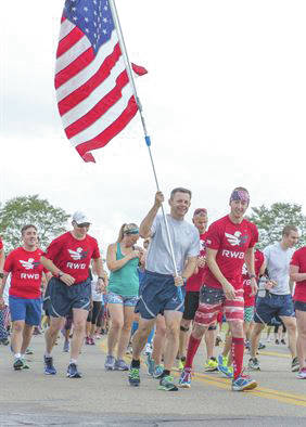 Submitted photo U.S. Air Force Col. Bradley McDonald, 88th Air Base Wing commander, holds the U.S. flag during the Run for the Fallen on Area B flight line at Wright-Patterson Air Force Base on Sept. 9, 2016. The Run for the Fallen provides an opportunity to remember and honor those who lost their lives and recognize those who continue to defend the nation.