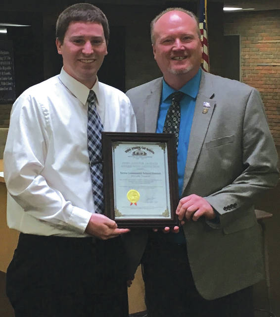 Submitted photo Xenia Community School District Treasurer Eric Soltis receives the Auditor of State Award with Distinction from Joe Braden.