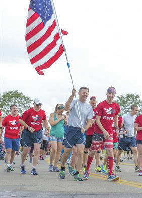 Submitted photo U.S. Air Force Col. Bradley McDonald, 88th Air Base Wing commander holds the U.S. flag during the Run for the Fallen on Sept. 9, 2016 on Area B flight line at Wright-Patterson Air Force Base. The Run for the Fallen provides an opportunity to remember and honor those who lost their lives and recognize those who continue to defend the nation.