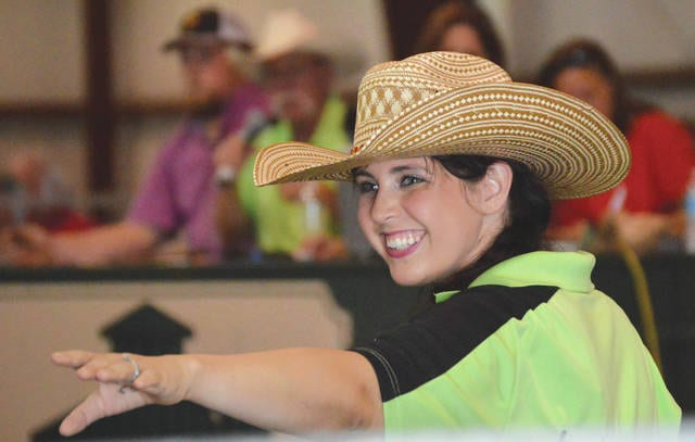 Samantha Gilliland, 26, working as the Ringman, offers a smile to a bidder during the Aug. 4 dairy auction at the Greene County Fair in Xenia.