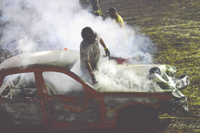 Jack Connor climbs through the front window to escape his burning demolition derby car, during the second heat of Street Stock competition, Monday July 31 at the Greene County Fair. Connor was unharmed in the fire.