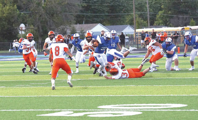 Xenia running back Sincere Wells (32) gets tripped up by Beavercreek linebacker Bryce Neuse (31) in Thursday's Aug. 24 high school football game at Xenia's Doug Adams Stadium. Beavercreek won the contest, 35-6.