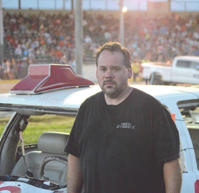 Steve Wilson of Xenia poses next to his 1995 Cadillac after competing in his first-ever demolition derby Monday, July 31 at the Greene County Fairgrounds in Xenia.