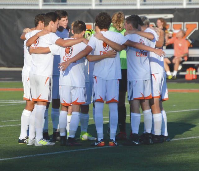 Members of the Beavercreek High School varsity boys soccer team huddle up before the start of Tuesday's scrimmage with Cincinnati St. Xavier, at Frank Zink Field in Beavercreek.