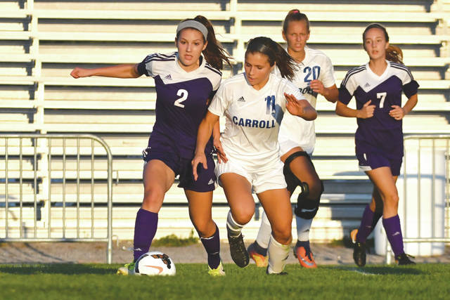 Bellbrook's Gabby Gerbic, a senior defender, battles for possession with Carroll's Alaina Casey, as Carroll's Eve Thorner (20) and Bellbrook's Audrey Spirk (7) look on, Sept. 16 in a non-league girls high school soccer match in Riverside.
