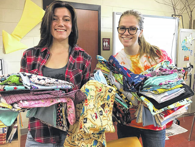 Submitted photo Cedarville National Honor Society members Ryanne Rinaldi (left) and Kaitlin Belliveau show pillow cases made for Dayton Children's Hospital.