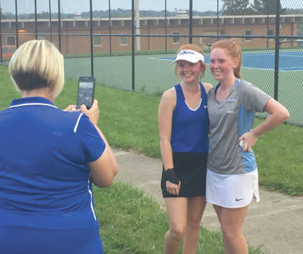 Xenia's Grace McClelland (left) and Fairborn's Paige Murry pose for a phone photo taken by Buccaneers coach Kay Scott, moments after the conclusion of Thursday's No. 1 singles match at Fairborn Community Park.
