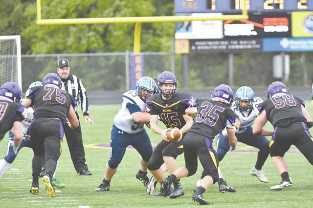 Bellbrook junior quarterback Brendan Labensky (15) hands off to junior running back Justin Sloan (35) during the first half of Friday's Sept. 1 game against Fairborn. Sloan led all rushers with 80 yards gained on 22 carries in Bellbrook's 12-6 win.