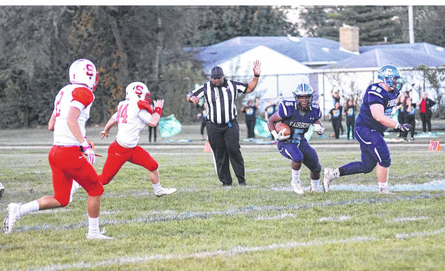 A game official steps back to get out of Fairborn runner K.J. Redmon's way, during first-half action Thursday, Sept. 28 against visiting Riverside Stebbins. Redmon scored three first-half touchdowns in the 38-0 Skyhawks win.