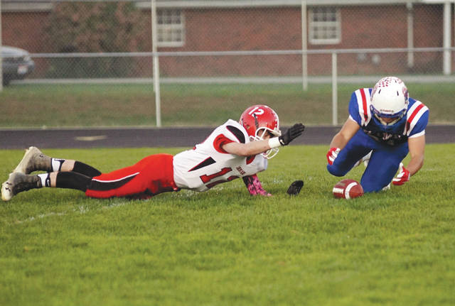 Cedarville quarterback Colby Cross (left) dives after a bad snap from center and Greeneview's Lane Goodbar pounces on the ball for a fumble recovery, in the first quarter of Friday's Oct. 13 Ohio Heritage Conference game at Don Nock Field in Jamestown.