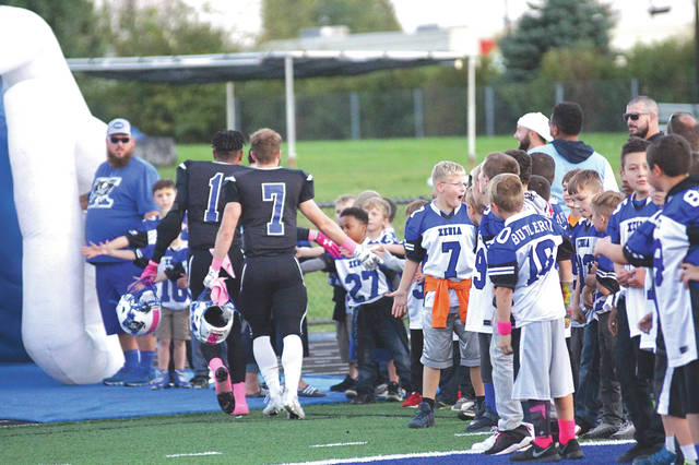 A Wee Bucs football player reacts after shaking the hand of current Xenia Buccaneers quarterback Jonny Shampton Jr. (7) and future Kentucky Wildcat Meechi Harris (1) prior to Friday's high school football game with Trotwood-Madison, at Doug Adams Stadium. It was Xenia's final home game of the season.