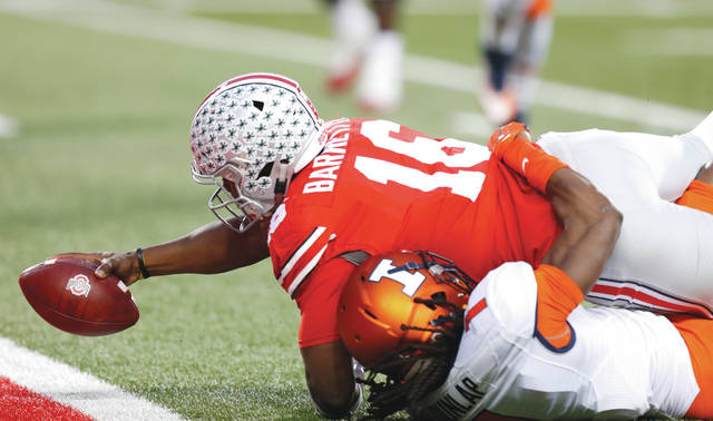 Ohio State quarterback J.T. Barrett reaches across the goal line for a touchdown as Illinois defensive back Jaylen Dunlap tries to make the a tackle during the first half of an NCAA college football game Saturday, Nov. 18, 2017, in Columbus, Ohio. (AP Photo/Jay LaPrete)