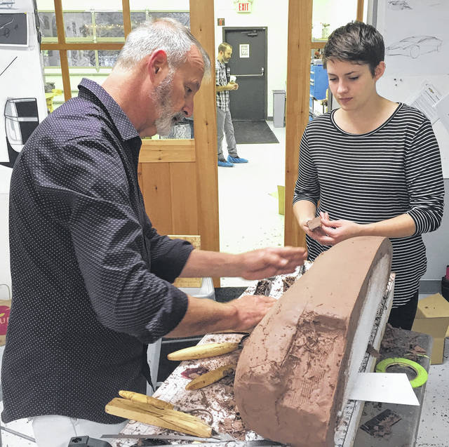 Don Grzebienik, clay sculpter for General Motors, works with Kadi Richardson from Cedarville University's innovative and industrial design program. Cedarville's program is ranked No. 5 in the United States according to CollegeValuesOnline.com.