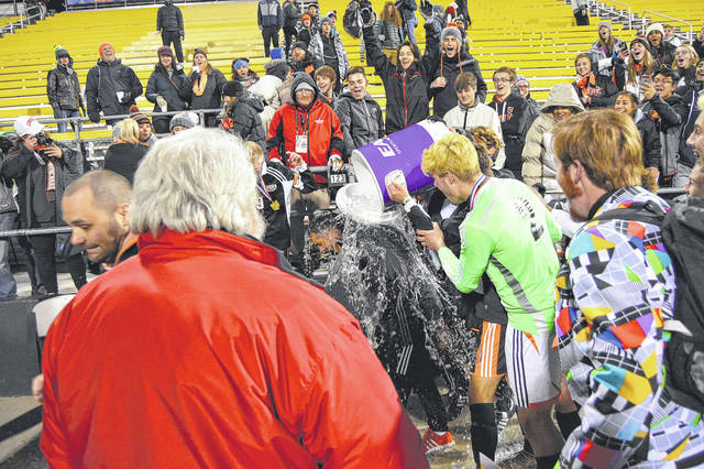 Beavercreek players douse Beavers assistant coach Jason Guiliano with a bucket of ice-cold water, Saturday night Nov. 11 after Beavercreek won the boys high school Division I state championship in double overtime, 1-0, over Medina, at MAPFRE Stadium in Columbus.