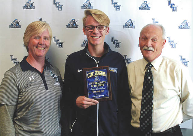 Senior distance runner Isaac Erlundson, center, shown with Legacy Christian Athletic Director Beverly Moser, and Mike Reed, was chosen as the Edward Jones Investments Athlete of the Month for September for Legacy Christian Academy High School. This award is being sponsored by the office of Mike Reed at Edward Jones Investments of Xenia, serving Xenia, Jamestown, Cedarville and surrounding areas. Erlundson broke the school record at the Centerville's Saturday Night Lights with a time of 16:28.5, and represented LCA at the state cross country championships this season. He is a talented athlete with a positive attitude and grade-point average over 4.0.