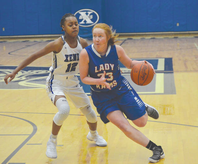 Greeneview's Faith Strickle (33) drives in for a score as Xenia's Trinity Morton-Nooks defends, during the girls high school basketball opener for both schools, Nov. 27, at Xenia High School. Strickle led all scorers with 18 points. Morton-Nooks led Xenia with 12.
