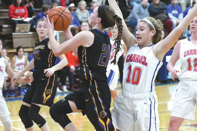 Bellbrook senior Cassidy Hofacker (21) drives past Carroll's Jillian Roberts (10) for a score during the first half of Wednesday's Dec. 13 girls high school basketball game at Carroll High School. Hofacker scored 11 points in Bellbrook's 48-45 win.