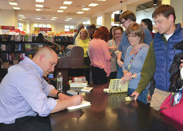 "Submitted photo AFRL Materials and Manufacturing Directorate engineer and author TJ Turner signs copies of his first book, ""Lincoln's Bodyguard,"" in April 2015."