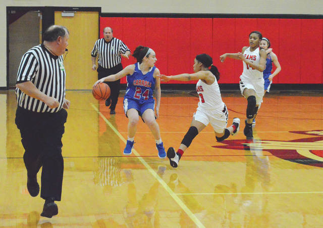 Carroll's Allie Stefanek (24) pulls up to let a Trotwood-Madison defender by, during first-half action at the Division II district semifinal game, Feb. 27 in New Carlisle. Carroll upset the second-seeded Rams, 52-41.