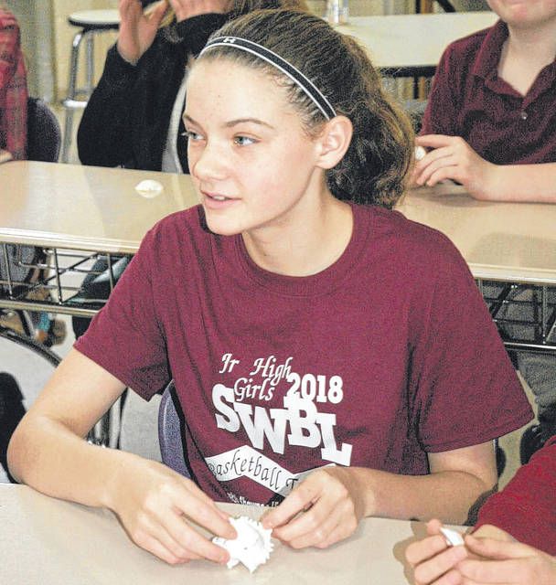 A Bellbrook Middle School student holds a seashell while listening to Emily Morgan speak.