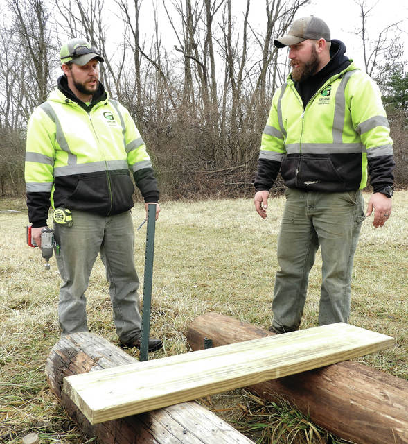 Submitted photos GCP&T Maintenance Team Member Jason Carter and GCP&T Maintenance Lead Allen Beam begin the installation of the third boardwalk bridge at the disc golf course.
