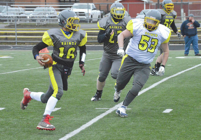Christopher Reed (16) of the Ohio Valley Saints grey team tries to elude the pursuit of the white team's Andrew Geesaman (53), in the team's March 24 intra-squad scrimmage at Clinton-Massie High School in Clarksville.
