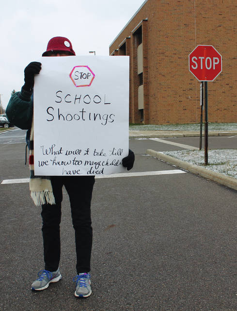 "Anna Bolton | Greene County News One month after a gunman claimed 17 lives in Marjory Stoneman Douglas High School, a Beavercreek resident, Robin, walked up and down the sidewalk in front of Beavercreek High School at 10 a.m. for 17 minutes, one minute for each victim. Robin protested gun violence March 14 at the same time students across the country participated in a national school walkout. She said the deaths were ""intolerable,"" and that action must be taken for all children."