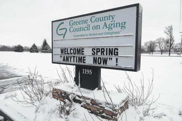 Submitted photo Senior Center Liaison Tim Brickey updated Greene County Council on Aging's sign March 21 with the coinciding of the first day of spring and an overnight snowfall. The council is located at 1195 W. Second St., Xenia.