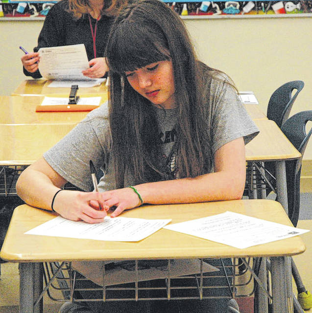 Ankeney Middle School student Corinna Ress works on her response to a prompt during round one of the PenOhio writing tournament.