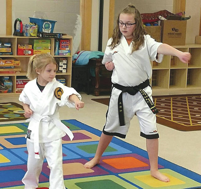 Submitted photo Madyson Bruce (on the right) teaches the beginners class, and she is instructing one of her students on martial arts moves.