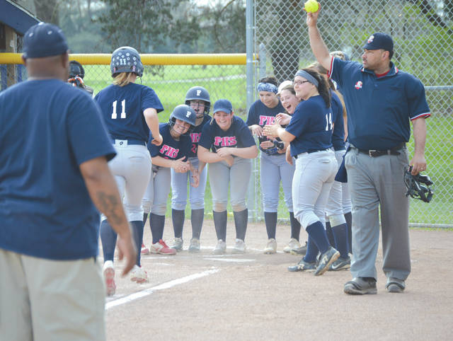 The Fairborn team awaits sophomore Ashlyn Baker (11) as she trots home with a solo home run to start the second inning, May 2 at Joan Dautel Field in Fairborn Community Park.