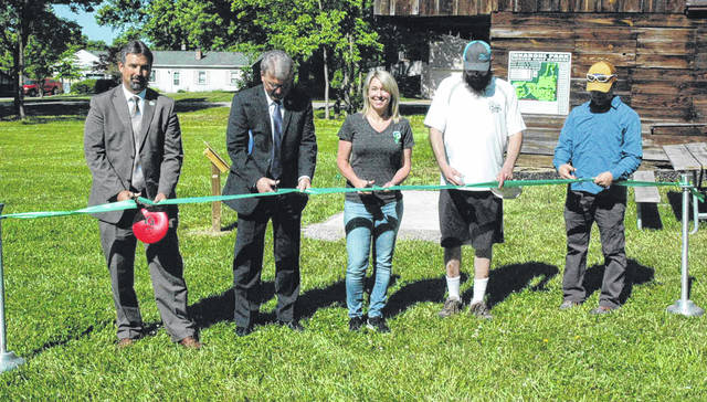 Scott Halasz | Greene County News Greene County Parks and Trails officially opened its new disc golf course at Karohl Park in Beavercreek. Cutting the ribbon are County Administrator Brandon Huddleson, County Commissioner Tom Koogler, Parks Commissioner Michelle Jenkins, Brian Crabtree from Hazy Shade Disc Golf, and Cedarville University professor of environmental science Dr. Mark Gathany.