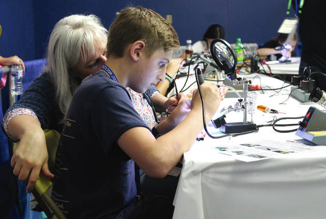 Anna Bolton | Greene County News Allison Mackey watches as her son Isaiah Mackey from Hanover, Indiana practices soddering in the Youth Tech area of Hamvention May 18. Isaiah's dad is a licensed amateur radio operator; this was their family's first time at Hamvention.