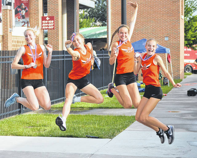 Members of the Beavercreek girls 3,200-meter relay team (left-to-right) Ashtyn Gluck, Taylor Ewert, Stephanie Pierce and Jodie Pierce celebrate for their friends and family by striking a pose with their silver medals, June 1 at the Division I state track and field championships in Columbus.