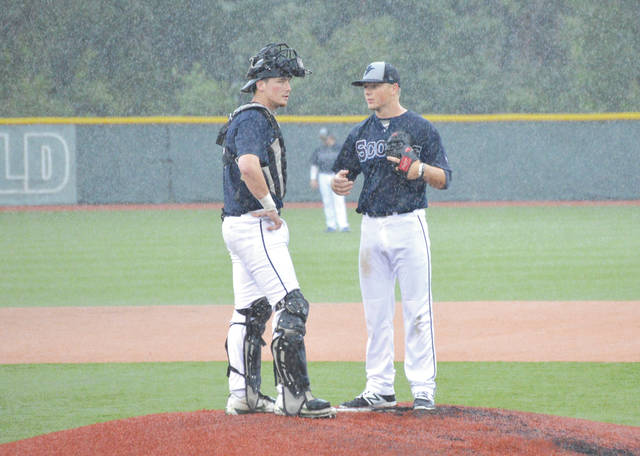 Catcher Conner Regan talks with Xenia Scouts starter Ben Bills on the mound during a heavy downpour, June 12 at Grady's Field, on the Athletes in Action Sports Complex in Xenia.
