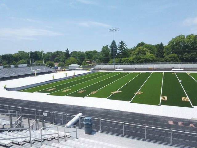 Workers put down the padding and new field turf June 7 at Frank Zink Field in Beavercreek.