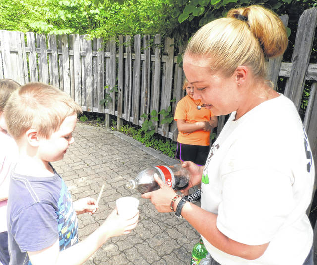 GCP&T Naturalist Ashlee Schmitt pours soda as part of the edible potion creating process at Minecraft Camp.