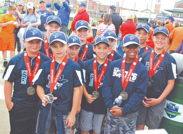 The Xenia Scouts 10U youth baseball team proudly shows off their Midwest Ohio Baseball League medals, June 23, at Fifth Third Field in Dayton.