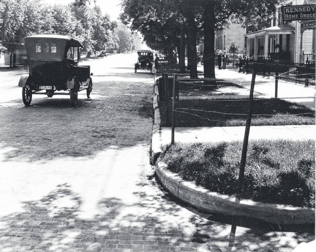 Courtesy of Greene County Historical Society A car drives the South side of East Main Street between Whiteman & Collier, circa 1920. Kennedy Home Groceries sign pictured at extreme right.