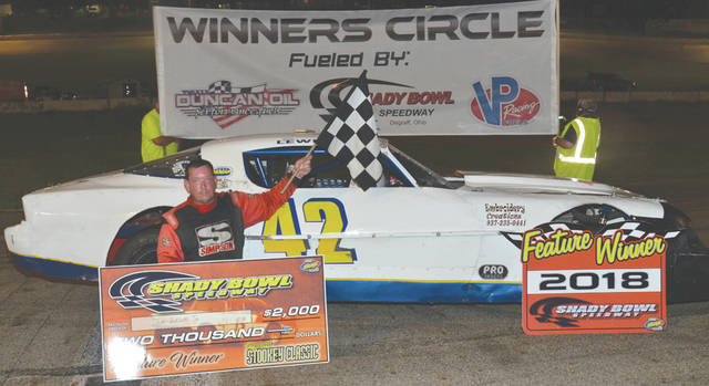 Jim Lewis Jr., of Fairborn, holds the checkered flag and the winner's check for $2,000 after winning the Kenny Stookey Classic Street Stocks race, July 14 at Shady Bowl Speedway in DeGraff.