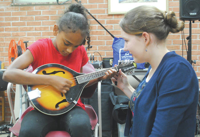 "The band members explained how each instrument works and, following the performance, offered a ""musical petting zoo"" in which children were invited to play and strum the bass, fiddle, mandolin, banjo and guitar."