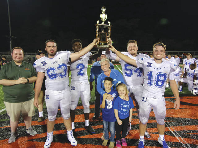 Submitted photo Captains of the Xenia High School football team hoist the Backyard Battle Trophy after a 41-14 win at Beavercreek Aug. 24. Xenia Mayor Sarah Mays (center) presented the trophy, with Beavercreek City Councilman Ryan Rushing (far left) and Beavercreek Mayor Bob Stone.